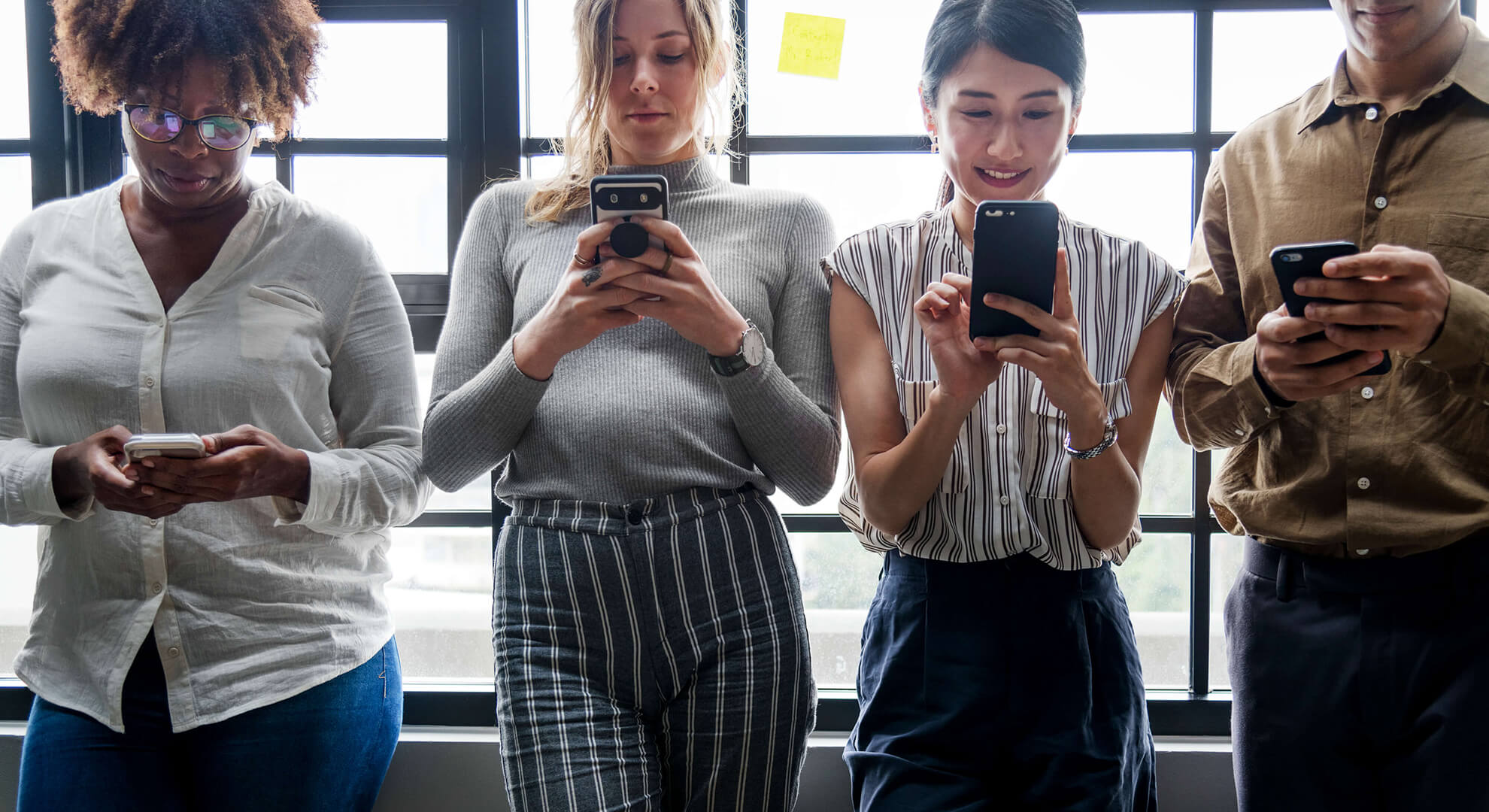 four people standing together all on their mobile phones