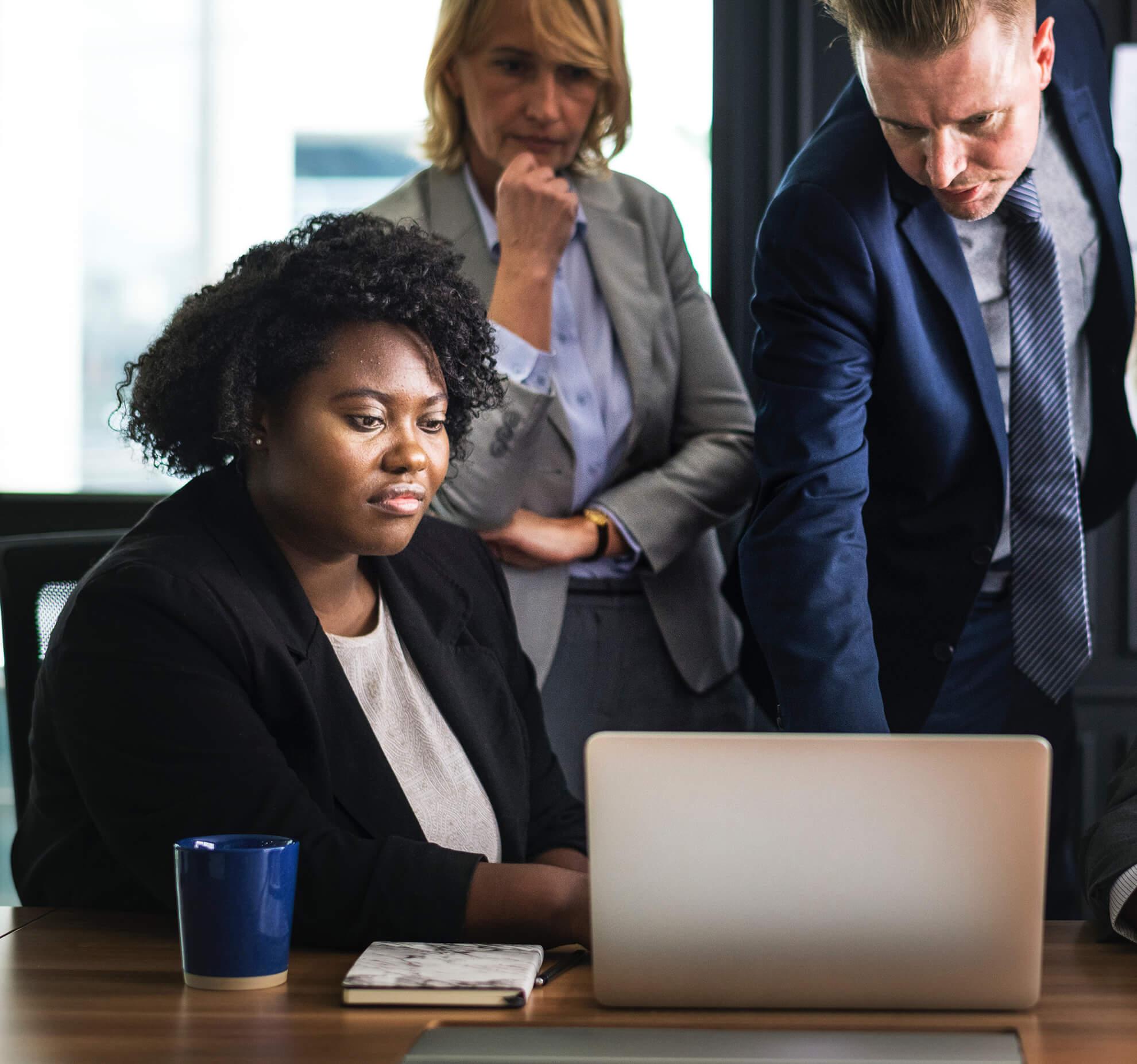three business professionals gathered around a laptop