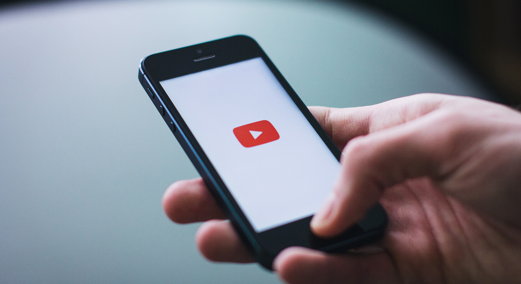 person holding phone and looking at YouTube app